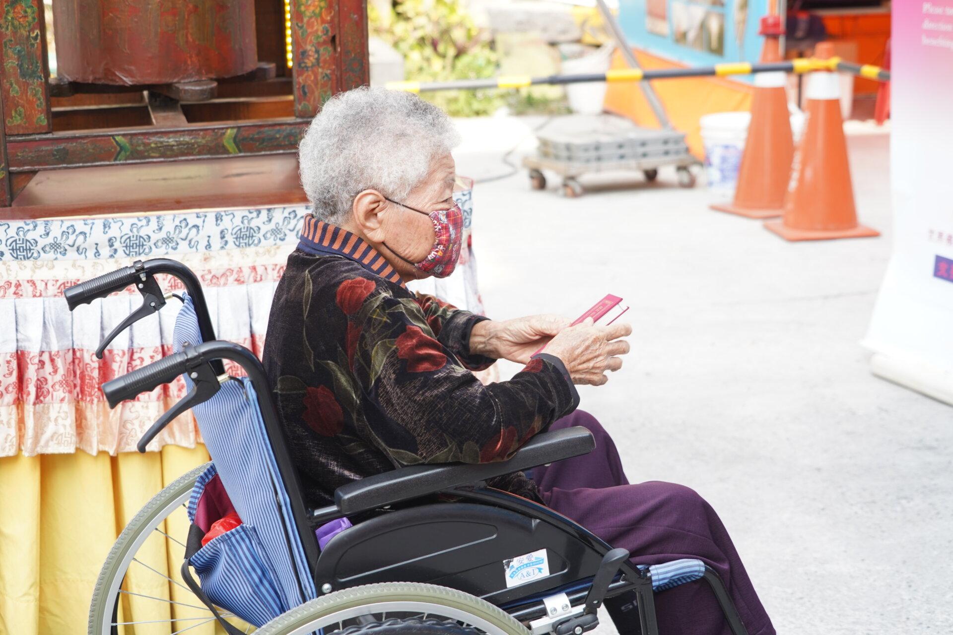 行動佛殿111站嘉義市地藏庵旁,年老的信眾坐著輪椅恭敬誦經