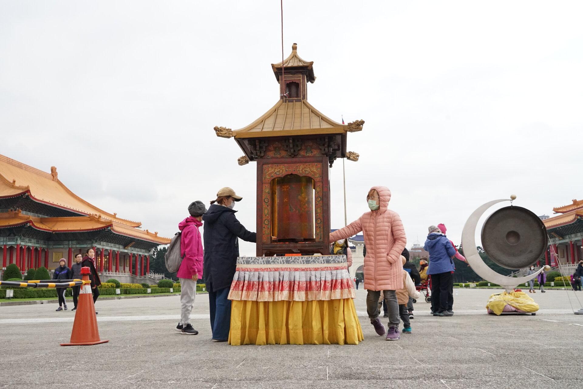 行動佛殿117站台北中正紀念堂,路過的民眾轉經輪祈求世界和平