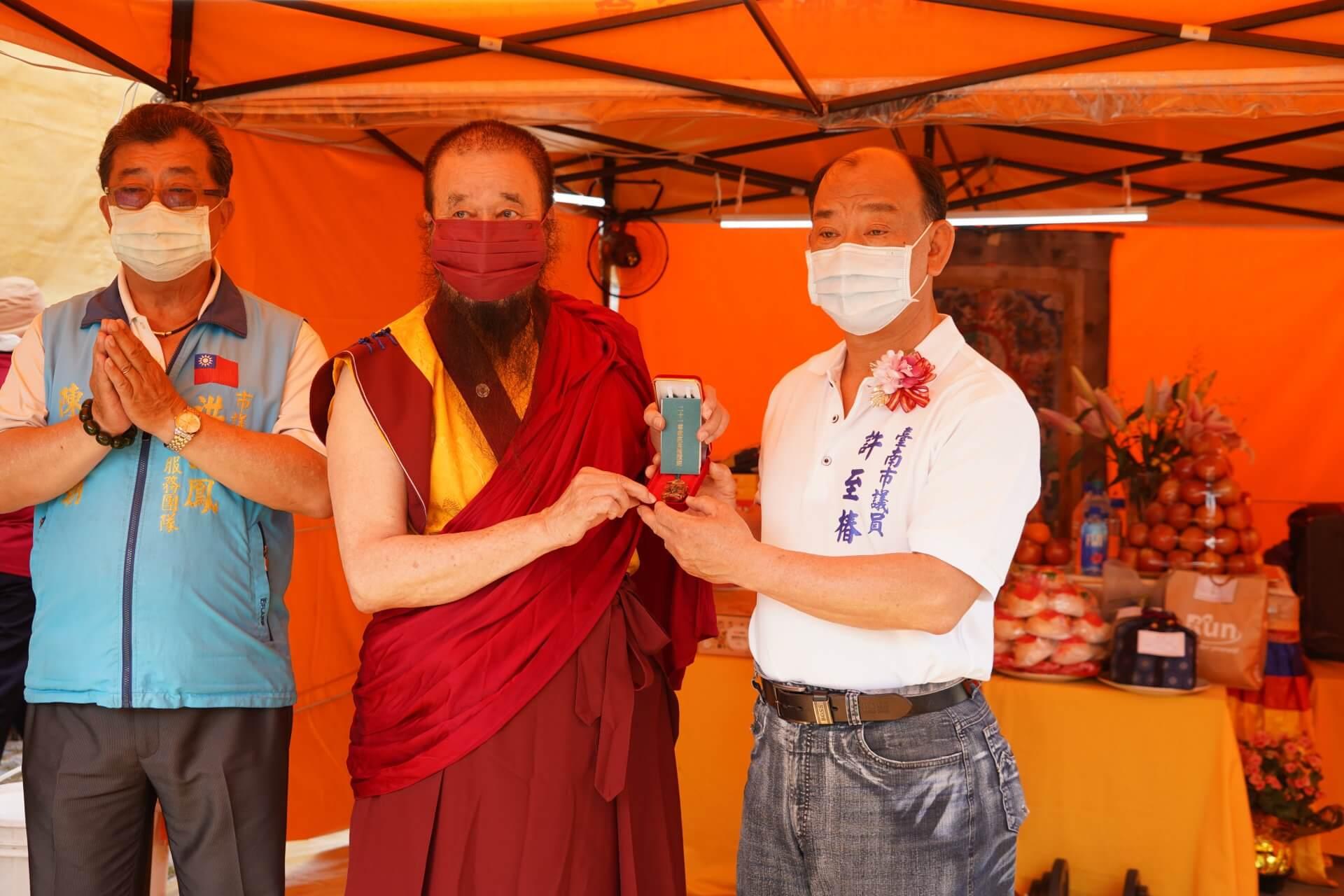 行動佛殿130站台南大興公園,本會指導上師恆性嘉措仁波且(左)致贈議員許至椿(右)珍貴加持物綠度母墜子